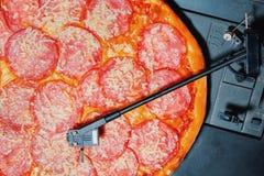 Italiensk pizza med salami som vinylrekordet som roterar på skivtallrikspelaren Peperoni begrepp av partiet med musik och royaltyfria foton