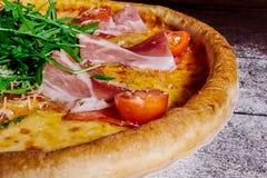 Italiensk pizza med skinka, tomater och örter på en trä½ för tabellï¿ att förlora upp royaltyfri bild