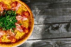 Italiensk pizza med skinka, tomater och örter på en trätabell arkivbild