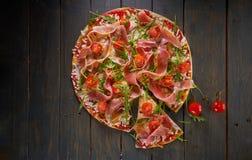 Italiensk pizza med skinka, tomater, ost och örter på tappningträbakgrund Top beskådar Royaltyfri Fotografi
