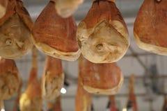 Italiensk prosciuttoskinka som hänger i slaktare` s, shoppar royaltyfri foto