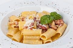 Italiensk rigatonipasta med prosciuttoen, parmesanost och bladet Arkivbilder