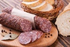 Italiensk salami som skivas på trätabellen Arkivbilder