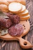 Italiensk salami som skivas på trätabellen Arkivfoto