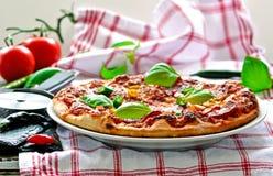 Italiensk salamipizza med basilika Royaltyfria Foton