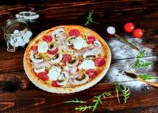 Italiensk snabbmat Läcker varm pizza som skivas och tjänas som på träuppläggningsfatet med ingredienser, övre sikt för slut Menyf royaltyfri foto