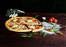 Italiensk snabbmat Läcker varm pizza som skivas och tjänas som på träuppläggningsfatet med ingredienser, övre sikt för slut Menyf arkivfoto