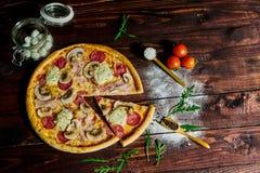 Italiensk snabbmat Läcker varm pizza som skivas och tjänas som på träuppläggningsfatet med ingredienser, övre sikt för slut Menyf arkivfoton
