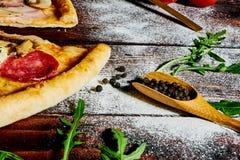 Italiensk snabbmat Läcker varm pizza som skivas och tjänas som på träuppläggningsfatet med ingredienser, övre sikt för slut Menyf royaltyfri bild