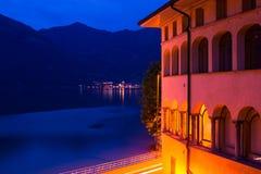 Italiensk stad för natt: en byggnad med upplysta bågar och en sikt av sjön Royaltyfria Bilder
