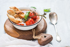 Italiensk tomat-, vitlök- och basilikasoppaPappa al Pomodoro i metallbunke med bröd på lantligt träbräde över ljus - blått fotografering för bildbyråer