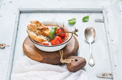 Italiensk tomat-, vitlök- och basilikasoppaPappa al Pomodoro i metallbunke med bröd på lantligt träbräde över ljus - blått arkivbilder