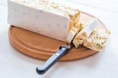 Italiensk torrone eller nougat med mandlar på en vit trätabell, slut upp med den utvalda fokusen fotografering för bildbyråer