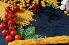 Italiensk traditionell mat, kryddor och ingredienser för att laga mat som basilika, körsbärsröda tomater, chilipeppar, vitlök och royaltyfria foton