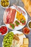 Italiensk uppsättning för antipastivinmellanmål Antipasto som sköter om uppläggningsfatet med knyckigt, salami, ost, druvor, oliv arkivbild