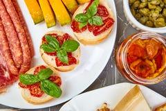 Italiensk uppsättning för antipastivinmellanmål Antipasto som sköter om uppläggningsfatet med knyckigt, salami, ost, druvor, oliv royaltyfri fotografi