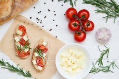 Italienska bruschettarostade bröd med tomater och ost på vit träbakgrund, bästa sikt royaltyfri foto