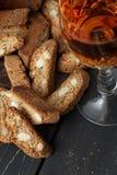Italienska cantuccinikex och ett exponeringsglas av vin Arkivfoto