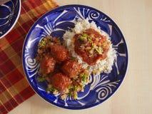 Italienska köttbullar med ett lokalt vridningrecept som inkluderar kryddig tomatsås för vita ris och skivad tomatlökar och persil arkivbild