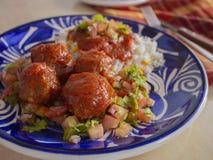 Italienska köttbullar med ett lokalt vridningrecept som inkluderar kryddig tomatsås för vita ris och skivad tomatlökar och persil royaltyfria bilder