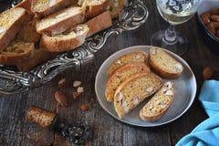 Italienska kakor: mandelcantuccini och exponeringsglas av vitt vin arkivfoton