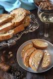 Italienska kakor: mandelcantuccini och exponeringsglas av vitt vin arkivbild