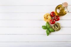Italienska och medelhavs- matingredienser på träbakgrund Körsbärsröda tomater pasta, basilikasidor och karaff med olivolja