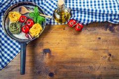 Italienska och medelhavs- matingredienser på träbakgrund Körsbärsröda tomater pasta, basilikasidor och karaff med olivolja Arkivbild