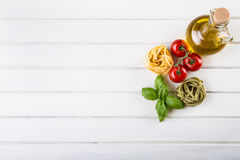 Italienska och medelhavs- matingredienser på träbakgrund Körsbärsröda tomater pasta, basilikasidor och karaff med olivolja Royaltyfria Foton