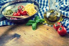 Italienska och medelhavs- matingredienser på träbakgrund Körsbärsröda tomater pasta, basilikasidor och karaff med olivolja Arkivfoto