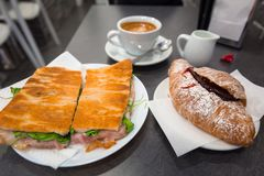 Italienskt kaffe med den driftstoppgifflet och smörgåsen på tabellen arkivbild