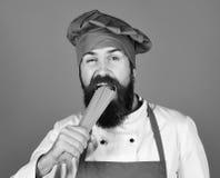 Italienskt kokkonstbegrepp Mannen eller hipsteren med skägget rymmer makaroni på blå bakgrund Kock med gruppen av spagetti kock royaltyfri fotografi