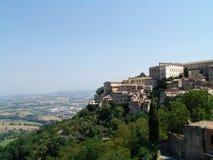 Italienskt landskap, gammal by på en grön kulle Träd och lantligt landskap Bakgrund Arkivbild