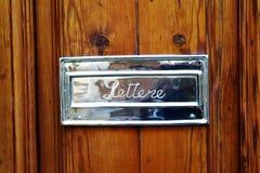 Italienskt mässingsbokstavshål på dörr Arkivfoto