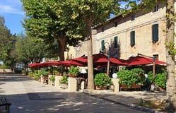 Italienskt utomhus- kafé med paraplyer och blomkrukor i liten släp Fotografering för Bildbyråer