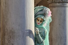 Italy – Venezia - Carnival  - Mask and  column. Italy - Venezia Carnevale. Plays a mask to hide behind a column, perhaps to invite you to follow Stock Photo