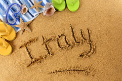 Italy Italian beach vacation writing. The word Italy written on a sandy beach, with scuba mask, starfish and flip flops Royalty Free Stock Photography