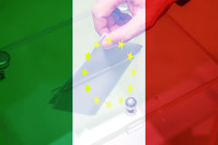 Italy Exit EU. Hand putting ballot in the box with Italy flag and yellow stars. Italian referendum on leaving the European Union Stock Photos