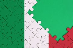 Italy flag is depicted on a completed jigsaw puzzle with free green copy space on the right side.  royalty free stock photography