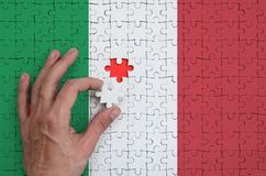 Italy flag is depicted on a puzzle, which the man`s hand completes to fold.  stock photos