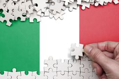 Italy flag is depicted on a table on which the human hand folds a puzzle of white color stock photos
