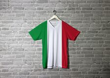 Italy flag on shirt and hanging on the wall with brick pattern wallpaper royalty free stock photography