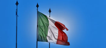 Italy flag waving on the wind. Italian flag waving in the blue sky Stock Image
