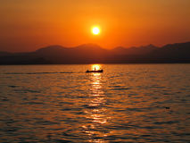 Italy, Lago di garda. Sunset over the Lago di Garda with a fish-boat Stock Photography