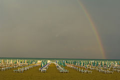 Italy, Lignano Beach with sunloungers, rainbow in background Stock Image