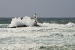 Italy, `Mangiabarche`, Storm. Waves smash against lighthouse or beacon. White waves, grey sky Stock Images