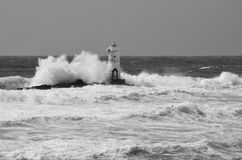 Italy, `Mangiabarche`, Storm. Waves smash against lighthouse or beacon. White waves, grey sky Stock Photo