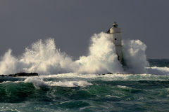 Italy, `Mangiabarche`, Storm. Waves smash against lighthouse or beacon. White waves, grey sky stock photos