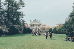 Italy, Milan, April 6, 2018: People walk in the park on the lawn. Italy, Milan, April 6, 2018: People walk in the park on a warm spring day royalty free stock image