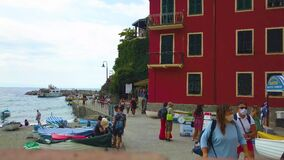 Italy, Monterosso - august, 2020. People in medical masks walk along the waterfront of the city of Monterosso. Houses, wooden boat
